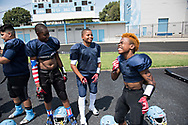 """While waiting to have their equipment checked before the game, Maxwell """"Bunchie"""" Young, 10, right, and his Hub City TarHeels teammates joke around, practicing their end zone dances."""