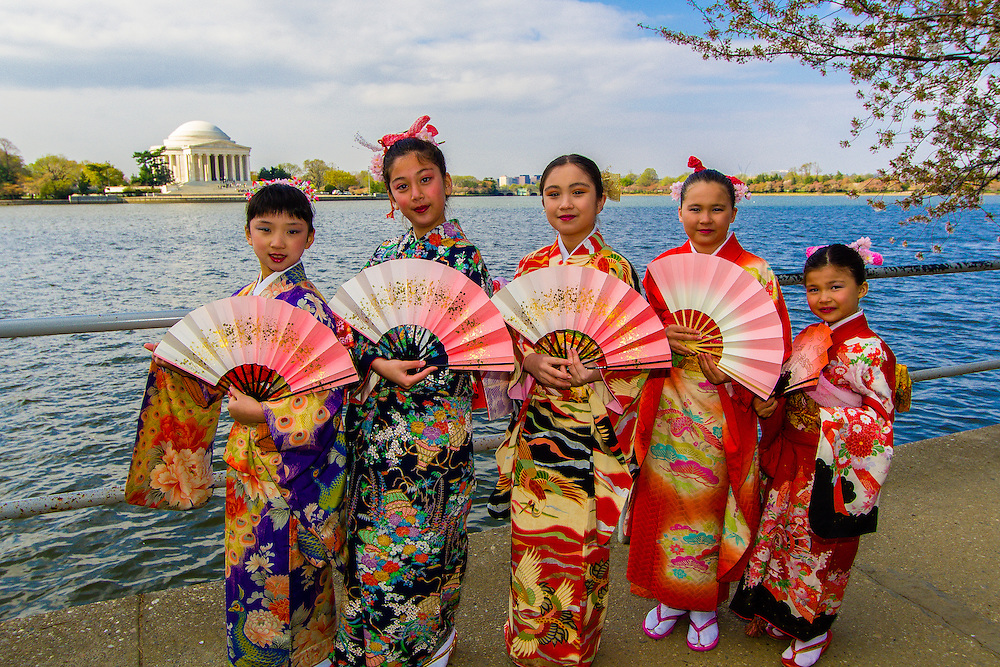 A group of Japanese-American girls in kimonos surrounded by cherry blossoms on the Cherry Tree Walk with Jefferson Memorial in background, the Tidal Basin, Washington, District of Columbia, USA