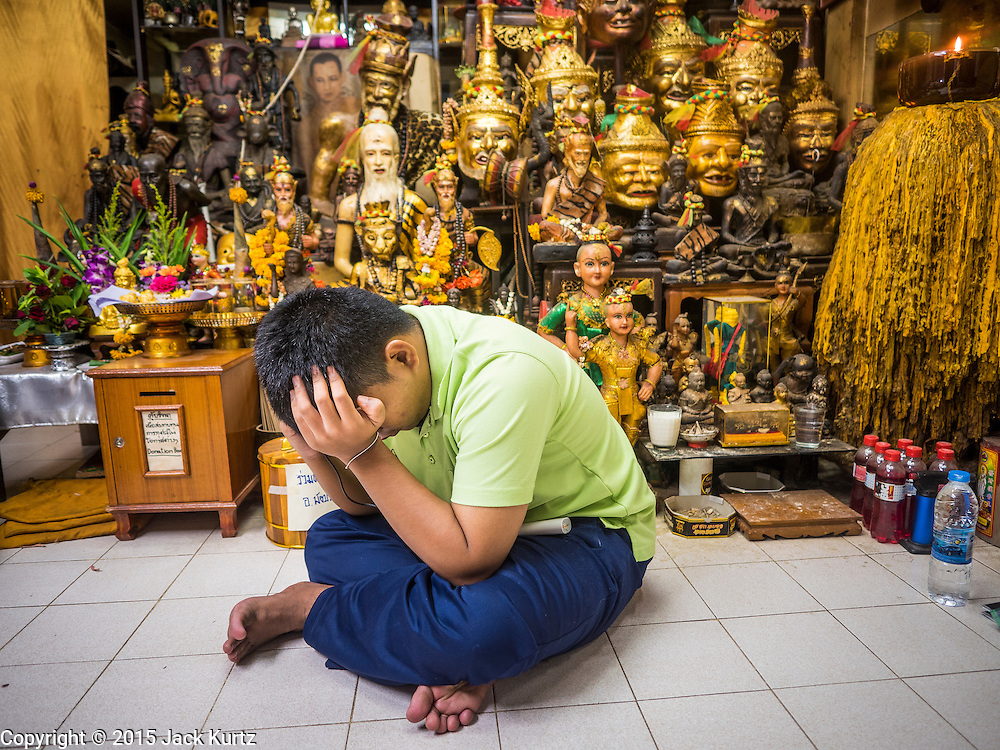 "27 MAY 2015 - BANGKOK, THAILAND: A blind man waits in the tattoo studio / chapel of Ajarn Neng Onnut in Bangkok. The man was there to have his tattoos, given to him by Ajarn Neng, blessed on his birthday. Ajarn Neng is a revered master of sacred tattoos and sees people all day at his Bangkok home. Sak Yant (Thai for ""tattoos of mystical drawings"" sak=tattoo, yantra=mystical drawing) tattoos are popular throughout Thailand, Cambodia, Laos and Myanmar. The tattoos are believed to impart magical powers to the people who have them. People get the tattoos to address specific needs. For example, a business person would get a tattoo to make his business successful, and a soldier would get a tattoo to help him in battle. The tattoos are blessed by monks or people who have magical powers. Ajarn Neng, a revered tattoo master in Bangkok, uses stainless steel needles to tattoo, other tattoo masters use bamboo needles. The tattoos are growing in popularity with tourists, but Thai religious leaders try to discourage tattoo masters from giving tourists tattoos for ornamental reasons.     PHOTO BY JACK KURTZ"