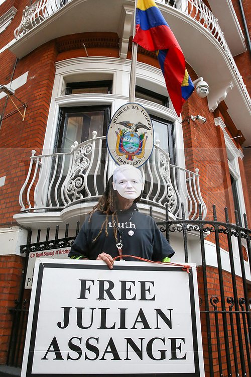 "© Licensed to London News Pictures. 05/04/2019. London, UK. A supporter of Julian Assange wearing a face mask holds a ""Free Julian Assange"" placard outside Ecuadorian Embassy in Knightsbridge. Media reports state that the Ecuadorian Embassy plan to remove Julian Assange, Wikileaks founder from the embassy within days. Julian Assange claimed political asylum in the Ecuadorean Embassy in June 2012 after he was accused of rape and sexual assault against women in Sweden. Photo credit: Dinendra Haria/LNP"