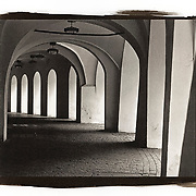 An exterior hallway of a building in Prague. The arches along the exterior highlight the contrast between light and darkness resulting from shadows against the white walls.