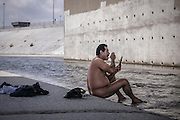 Los Angeles, California, U.S. - <br /> <br /> Life On The Edge<br /> <br /> According to the Los Angeles Homeless Services Authority, the homeless population of Los Angeles and L.A. County has increased as much as 20% in the last year, and leads the nation in homeless unsheltered living, at nearly 70%.<br /> Homelessness here has grown substantially since the last El Niño, which dumped 30 inches of rain on Los Angeles during the winter of 1997-98, authorities say. Recently, the Los Angeles City Council declared a state of emergency on homelessness and called for $100 million to help address the growing crisis. The Los Angeles River flows through Los Angeles County, from Canoga Park in the western end of the San Fernando Valley, nearly 48 miles southeast to its mouth in Long Beach. Homeless people live along much of its length, with many located generally east of Downtown L.A., making their homes in and around the river, under overpasses or alongside rail lines and industrial wastelands. Those people - many dealing with disability, mental health and criminal justice issues - living in tents, improvised shelters and live-in vehicles, have increased 85% in the same period. Causes include high unemployment, low wages and escalating rents, coupled with gentrification and elimination of SRO hotels and cheap rooms, a last option for many. An estimated 800 people live in LA's riverbeds and storm drains, which will be deluged with powerful torrents when El Niño storms arrive in early 2016. Although the Sheriff's Department and LA's Homeless Services Authority have made numerous visits to warn residents, many see no compelling reason - or options - for moving. Most are not the transient homeless we are used to seeing but have set up semi-permanent living quarters in the LA River, which with its sweeping concrete vistas and city skyline sunsets may soon become both a beautiful and dangerous place to call home.<br /> <br /> An unidentified man bathes and shaves in the L.A. Rive