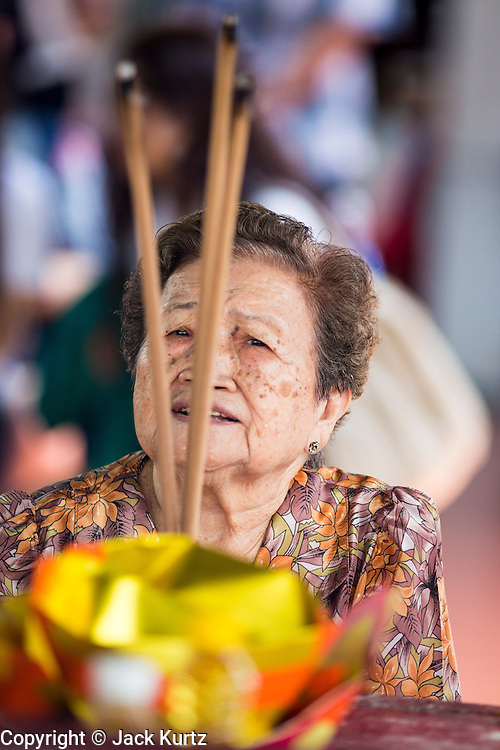 "26 AUGUST 2013 - BANGKOK, THAILAND: A woman prays before donating rice donating to the Poh Teck Tung Foundation for Hungry Ghost Month in Bangkok. Poh Teck Tung operates hospitals and schools and provides assistance to the poor in Thailand. The seventh lunar month (August - September in 2013) is when the Chinese community believes that hell's gate will open to allow spirits to roam freely in the human world for a month. Many households and temples will hold prayer ceremonies throughout the month-long Hungry Ghost Festival (Phor Thor) to appease the spirits. During the festival, believers will also worship the Tai Su Yeah (King of Hades) in the form of paper effigies which will be ""sent back"" to hell after the effigies are burnt.      PHOTO BY JACK KURTZ"