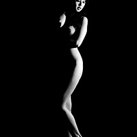 Nude Asian woman poses against black background