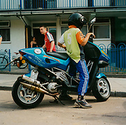 Young boy playing on a motorbike outside a housing estate