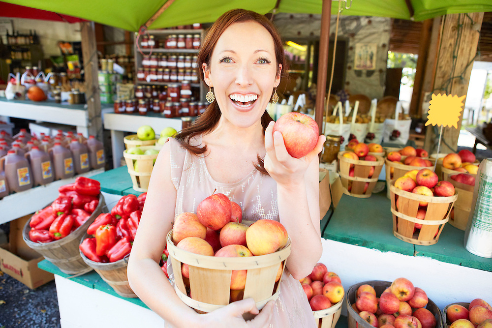 Lifestyle image of smiling girl with red apple basket in front of farmer's market