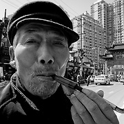 A man somoking in a traditional tobacco pipe (Chinese tobacco pipes are generally composed of three parts: a small bowl of metal (copper alloy), a stem of bamboo (preferred over wood), and a mouthpiece of stone (sometimes jade, ivory, or glass), Old Town Gate intersection of South Henan road, Hangpu District, Shanghai, China, Asia