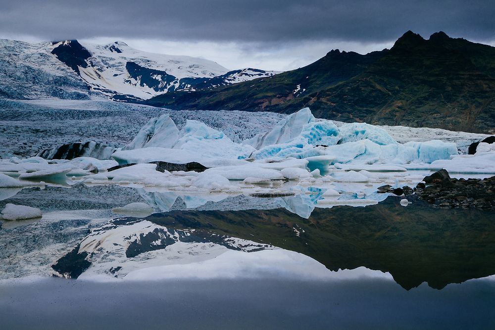 Broken icebergs collect in a fresh water lake below the Vatnajokul Glacier on an overcast day in Iceland.