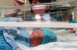 Nurse feeds milk to premature baby in neo-natal intensive care unit; Liverpool Women's Hospital UK