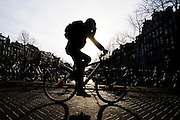 In Amsterdam fietst een man over een brug. Hij houdt de hand tegen zijn hoofd.<br /> <br /> In Amsterdam a man cycles on a bridge. He is putting his hand against his head.