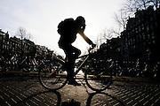 In Amsterdam fietst een man over een brug. Hij houdt de hand tegen zijn hoofd.<br /> <br /> In Amsterdam a man cycles on a bridge. He is putting his hand against his head.