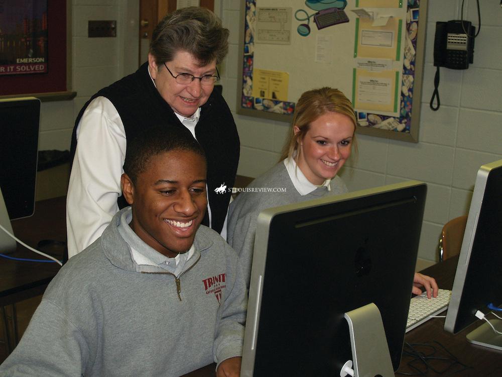 Sister Karl Mary Winkelmann, SSND, president of Trinity Catholic High School, assists seniors Natalie Fish and Aaron Johnson.