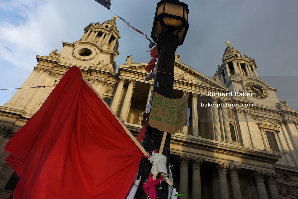 Red flag and anti-capitalist slogan on the 11th day of the Occupy London protest camp in St Paul's cathedral churchyard, London 26/11/11. City lawyers are using medieval pedestrian bylaws to gain a court injunction to evict the activists who set up tents and shelters as in other countries.