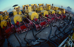 Stock photo of a row of 10,000 hp pumps used during frac operation in oilfield