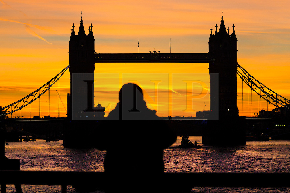 © Licensed to London News Pictures. 25/01/2016. London, UK. A man watches colourful sky behind Tower Bridge just ahead of sunrise and mild weather this morning.  Photo credit : Vickie Flores/LNP