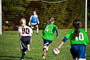 Youth soccer girl dribbles soccer ball to the goal.