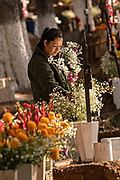 A woman decorates a gravesite of a family member with marigolds for the Day of the Dead festival October 31, 2017 in Tzintzuntzan, Michoacan, Mexico.