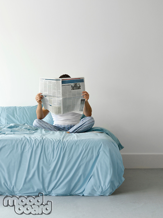 Man sitting on bed reading newspaper