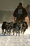 John Alexander and his eight dog sled team head down the starting straight away of the Kalkaska Winterfest course just after sunrise during the final day of the events scheduled racing.