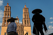 Mariachi performers are silhouetted in front of the Parroquia Nuestra Señora de Dolores Catholic Church also called the Church of our Lady of Sorrows at the Plaza Principal in Dolores Hidalgo, Guanajuato, Mexico. Miguel Hildago was a parish priest who issued the now world famous Grito - a call to arms for Mexican independence from Spain.