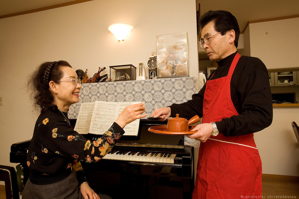 Hayashi Yoshitake (65) - reformed husband - offering coffee to his wife Takeko Yoshitake (65) when she is having a break from playing piano. They are both middle school teachers, she teaches music. They have been married for 39 years.  Tokyo 9 Feb. 2007