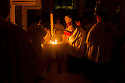 DENVER, CO - APRIL 19: Archbishop Samuel J. Aquila, center, reads from scripture held by John Brooks, right, during the Easter Vigil Mass at the Cathedral Basilica of the Immaculate Conception on April 19, 2014, in Denver, Colorado. (Photo by Daniel Petty/Denver Catholic Register)
