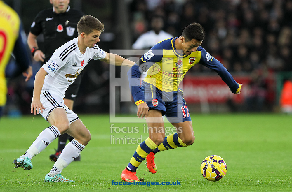 Tommy Carroll (left) of Swansea City puts Alexis S&aacute;nchez (right) of Arsenal under some pressure during the Barclays Premier League match at the Liberty Stadium, Swansea<br /> Picture by Tom Smith/Focus Images Ltd 07545141164<br /> 09/11/2014