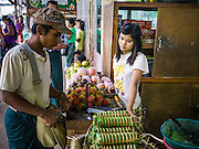 14 JUNE 2013 -  SAMALAUK, AYEYARWADY, MYANMAR:  A man buys fruit at a highway rest stop on Highway 5 in Samalauk, Ayeyarwady, in the Irrawaddy delta region of Myanmar. Most Burmese men join the clergy at least once in the lives, sometimes for just a few weeks, other times for a lifetime commitment. This region of Myanmar was devastated by cyclone Nargis in 2008 but daily life has resumed and it is now a leading rice producing region.  PHOTO BY JACK KURTZ
