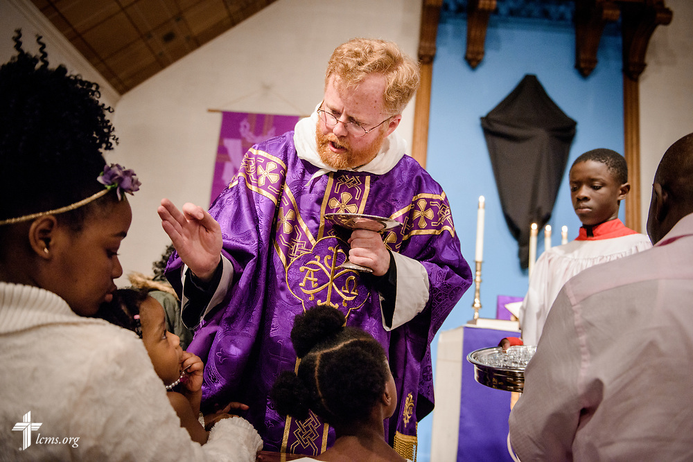 The Rev. Roy Axel Coats, pastor of Lutheran Church of the Redeemer, Baltimore, blesses a child during Communion on Palm Sunday, March 25, 2018. LCMS Communications/Erik M. Lunsford
