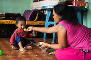 Nanimaiya Tamang (31) feeds her nephew Sujal Tamang (2) who is now living with her in her apartment in Jorpati, Kathmandu, Nepal on 2 July 2015. Sujal was buried under the rubble of his collapsed house for 36 hours before rescuers found him injured with a broken leg next to his mother who was killed on the spot. Photo by Suzanne Lee for SOS Children's Villages