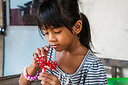 Een familielid van Sron Sothy speelt met kunstbloemen. Ze woont met haar familie vlakbij de fabriek waar ze werk. Sron Sothy werkt bij Chu Hsing in Phnom Penh, een van de vele kledingfabrieken in Cambodja. Sothy is tevens de president van de vakbond C.CAWDU bij de fabriek.
