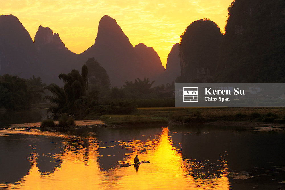 Fishing raft on the Li River with reflection of karst hills at sunset, Yangshuo, Guangxi Province, China