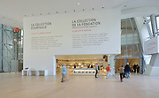 Entrance hall and bookshop inside the Fondation Louis Vuitton, an art museum and cultural centre designed by Frank Gehry, b. 1929, and built 2008-14, next to the Jardin d'Acclimatation in the Bois de Boulogne, in the 16th arrondissement of Paris, France. In the distance are the towers of La Defense. The building resembles the sails of a boat and houses 11 galleries, an auditorium seating 350 and roof terraces. Picture by Manuel Cohen
