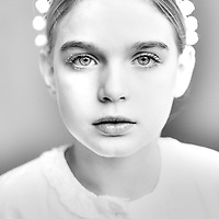 Young girl looking at camera wearing white clothes and headband with pom poms