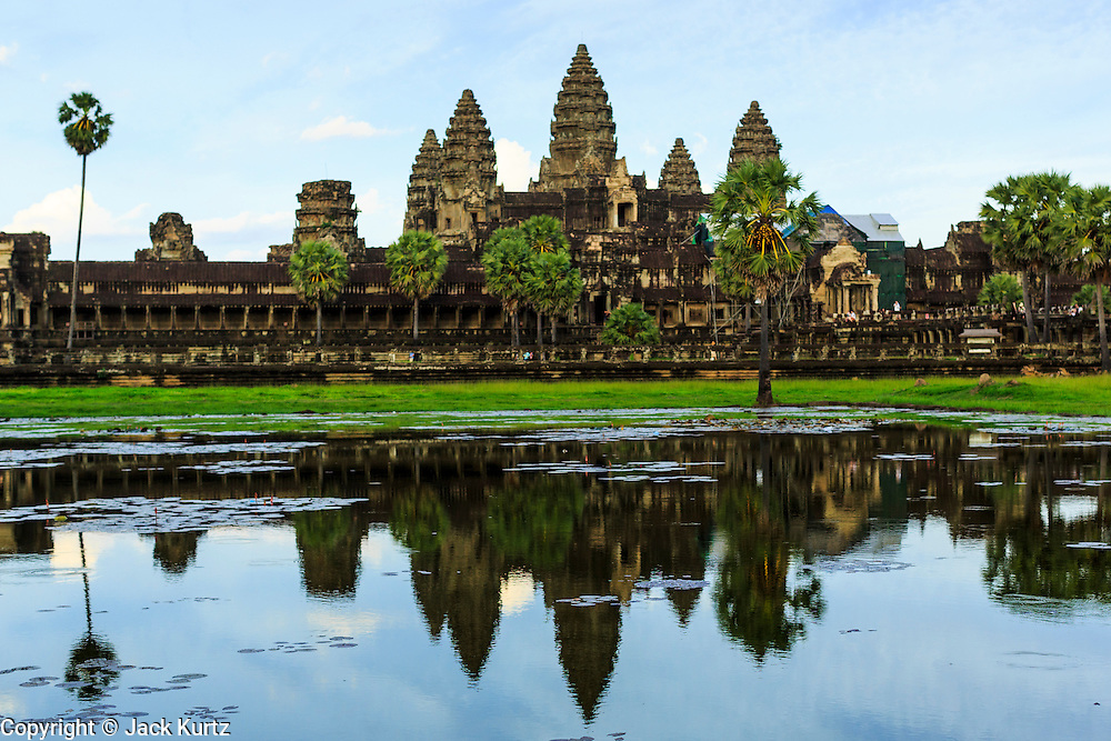 "02 JULY 2013 - ANGKOR WAT, SIEM REAP, SIEM REAP, CAMBODIA:  The west side of Angkor Wat late in the afternoon. Angkor Wat is the largest temple complex in the world. The temple was built by the Khmer King Suryavarman II in the early 12th century in Yasodharapura (present-day Angkor), the capital of the Khmer Empire, as his state temple and eventual mausoleum. Angkor Wat was dedicated to Vishnu. It is the best-preserved temple at the site, and has remained a religious centre since its foundation – first Hindu, then Buddhist. The temple is at the top of the high classical style of Khmer architecture. It is a symbol of Cambodia, appearing on the national flag, and it is the country's prime attraction for visitors. The temple is admired for the architecture, the extensive bas-reliefs, and for the numerous devatas adorning its walls. The modern name, Angkor Wat, means ""Temple City"" or ""City of Temples"" in Khmer; Angkor, meaning ""city"" or ""capital city"", is a vernacular form of the word nokor, which comes from the Sanskrit word nagara. Wat is the Khmer word for ""temple grounds"", derived from the Pali word ""vatta."" Prior to this time the temple was known as Preah Pisnulok, after the posthumous title of its founder. It is also the name of complex of temples, which includes Bayon and Preah Khan, in the vicinity. It is by far the most visited tourist attraction in Cambodia. More than half of all tourists to Cambodia visit Angkor.         PHOTO BY JACK KURTZ"