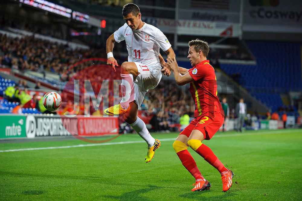 Aleksandar Kolarov of Serbia (Manchester City) is challenged by Chris Gunter of Wales (Reading) during the first half of the match - Photo mandatory by-line: Rogan Thomson/JMP - Tel: Mobile: 07966 386802 10/09/2013 - SPORT - FOOTBALL - Cardiff City Stadium - Cardiff -  Wales V Serbia- World Cup Qualifier.