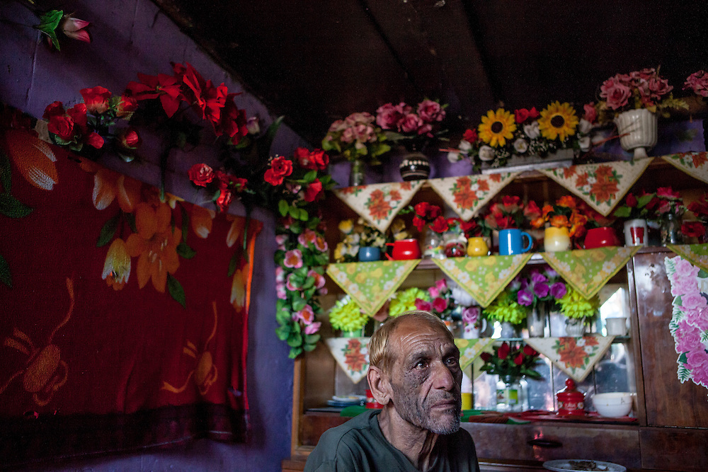"""Portrait of Stephan nicknamed """"Longa"""" in his home at the Roma settlement. He is in love with flowers and has decorated his whole interior with many different types. """"Budulovskej Street"""" is a segregated Roma settlement which is located about 2 km behind the Slovak village of Moldava nad Bodvou."""