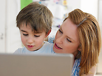 Mother and son (3-6) using laptop indoors