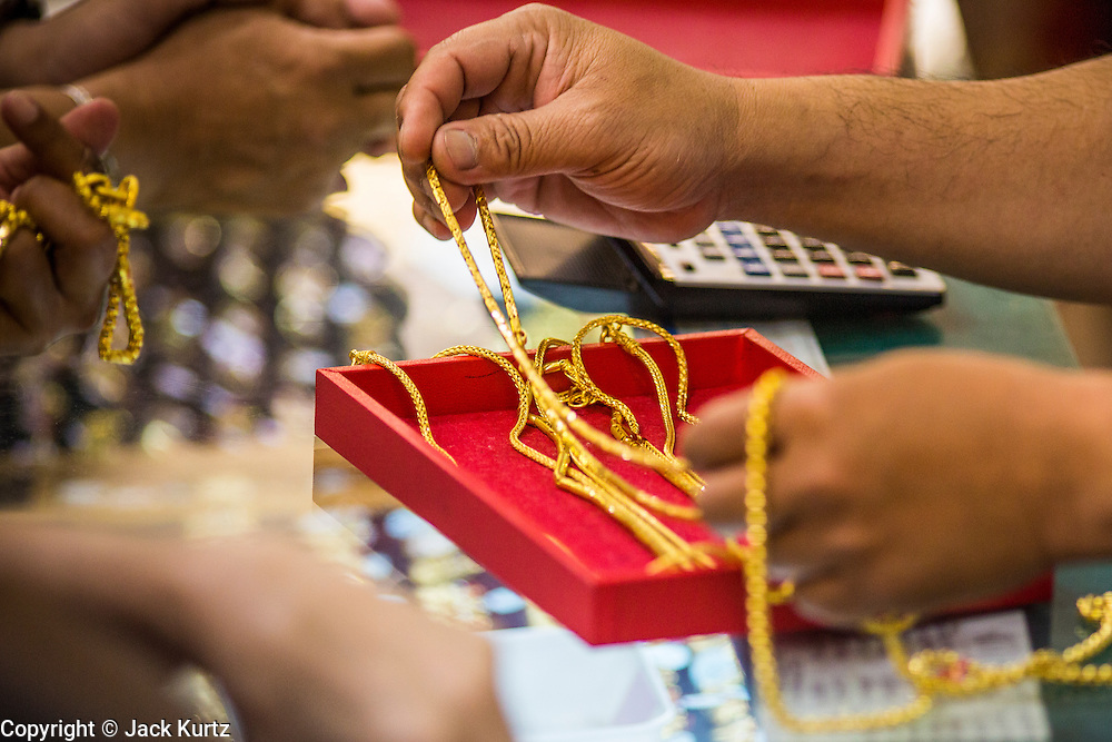 17 APRIL 2013 - BANGKOK, THAILAND:   An employee in a Bangkok gold shop lays out gold chains for a customer to look at Wednesday. Thais flocked to gold shops in Bangkoks's Chinatown this morning to buy gold. Wednesday was the first day most gold shops were open after a five day holiday weekend. Shops were closed Friday through Tuesday, when global gold prices dropped by more than 13% based on jitters that Cyprus might liquidate its gold stocks. The Thailand Futures Exchange (TFEX) suspended trading of all gold and silver futures for a short time Tuesday morning because of instability in the market. Gold is now about 22 percent below the record peak of $1,920.30 an ounce set in September 2011. Thais buy gold as both jewelry and an investment, a hedge against inflation and financial failures. Bangkok's Chinatown district is the center of Thailand's gold trade.   PHOTO BY JACK KURTZ