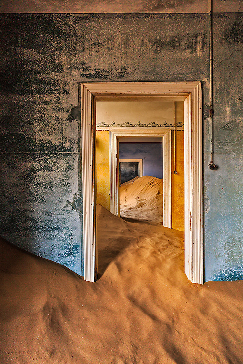 Reflected sunlight, fading paint, and multiple door frames create interesting colors and shapes, as the desert reclaims its own.