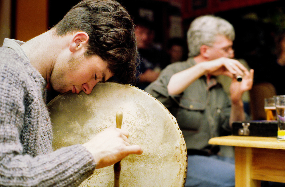 Traditional Irish pub musicians playing bodhran and flute music in a bar in the town of Bantry, County Cork, south west Ireland.