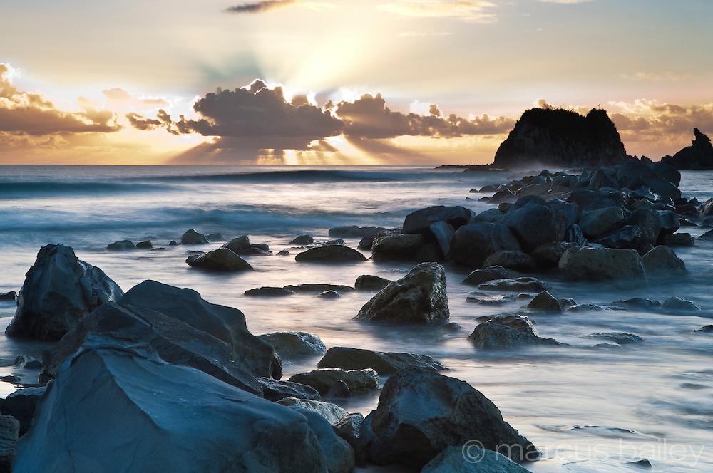 sea water breaking over sea rocks at sunrise, mangawhai, northland, new zealand
