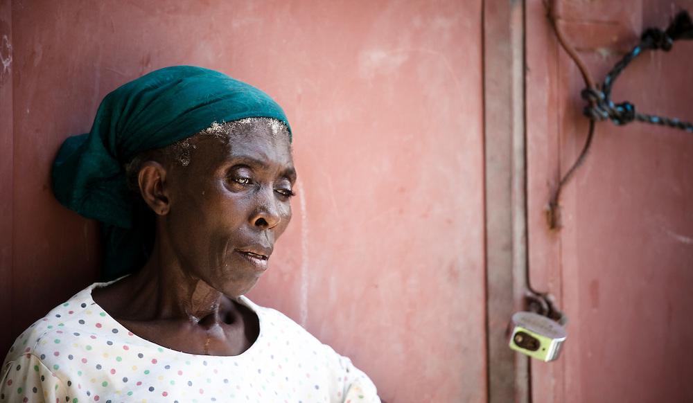 Woman wearing green bandana against red door