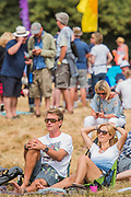 Relaxing in the sun in teh Obelisk Arena -0 The 2018 Latitude Festival, Henham Park. Suffolk 13 July 2018
