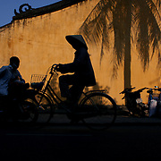 A street scene in Hoi An, Vietnam as a local rides past a bright yellow colours wall on a bike. Hoi An is an ancient town and an exceptionally well-preserved example of a South-East Asian trading port dating from the 15th century. Hoi An is now a major tourist attraction because of its history. Hoi An, Vietnam. 5th March 2012. Photo Tim Clayton
