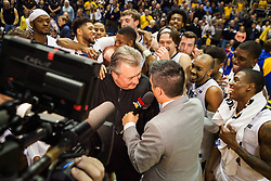 Dec 17, 2016; Morgantown, WV, USA; West Virginia Mountaineers head coach Bob Huggins is surrounded by players after the game as they celebrate Huggins reaching 800 career wins at WVU Coliseum. Mandatory Credit: Ben Queen-USA TODAY Sports