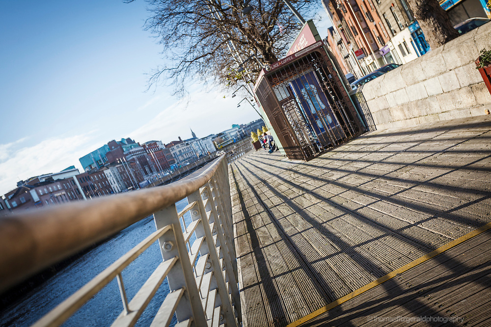 2012: Dublin, Ireland. A closeup of the shadows falling on the boardwalk that runs beside the river Liffey in Dublin