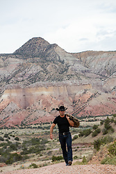 cowboy walking on a dirt road overlooking a mountain range