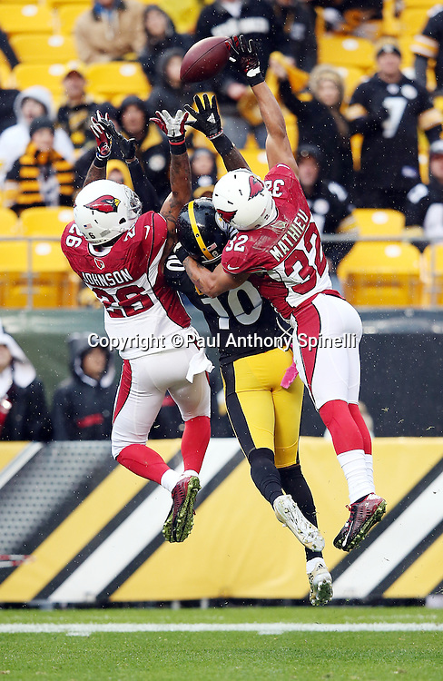 Arizona Cardinals free safety Rashad Johnson (26) and Arizona Cardinals free safety Tyrann Mathieu (32) jump and break up a deep pass intended for Pittsburgh Steelers wide receiver Martavis Bryant (10) during the 2015 NFL week 6 regular season football game against the Pittsburgh Steelers on Sunday, Oct. 18, 2015 in Pittsburgh. The Steelers won the game 25-13. (©Paul Anthony Spinelli)