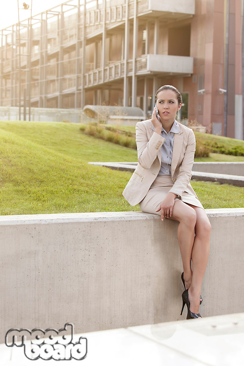 Full length of young businesswoman using cell phone while sitting on wall against office building